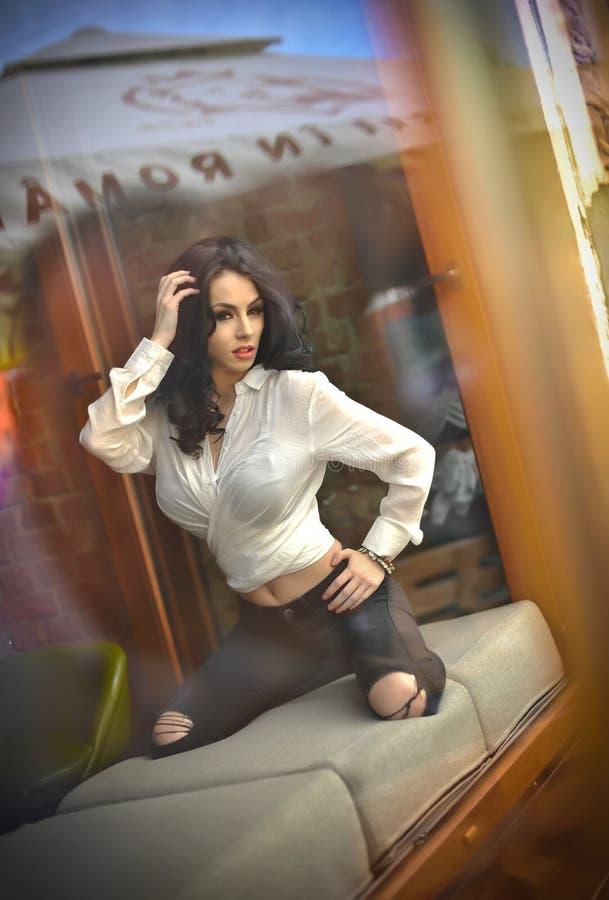 Привлекательное сексуальное брюнет в белой плотной рубашке и черноте пригонки сорвало джинсы представляя провокационно в оконной  стоковое изображение rf
