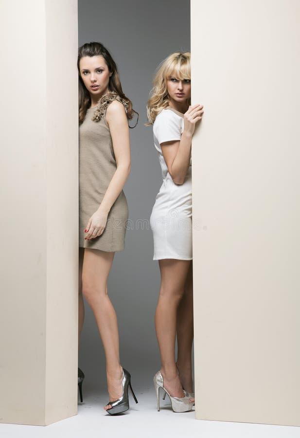 Привлекательные женщины пряча theirselves за стеной стоковое фото rf