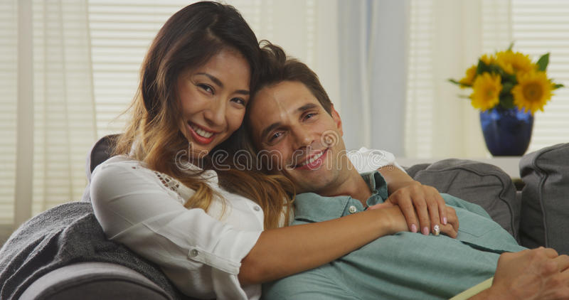 Привлекательные межрасовые пары сидя на кресле стоковые изображения