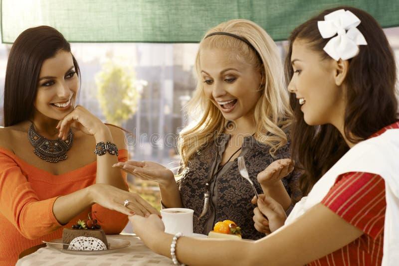 Молодая женщина показывая обручальное кольцо к друзьям стоковое изображение