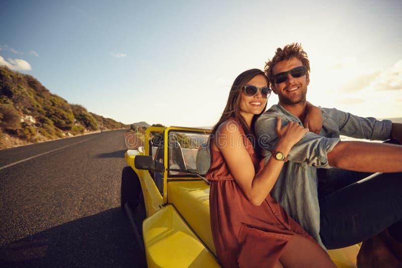Привлекательные молодые пары сидя на клобуке их автомобиля стоковые изображения rf