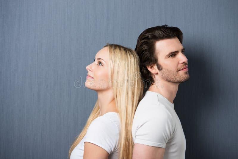 Привлекательные молодые пары стоя спина к спине стоковая фотография