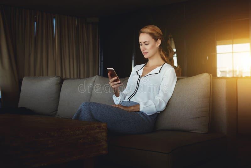Привлекательные новости чтения женщины в интернете через телефон клетки во время бизнес-ланча в удобном ресторане, стоковые изображения
