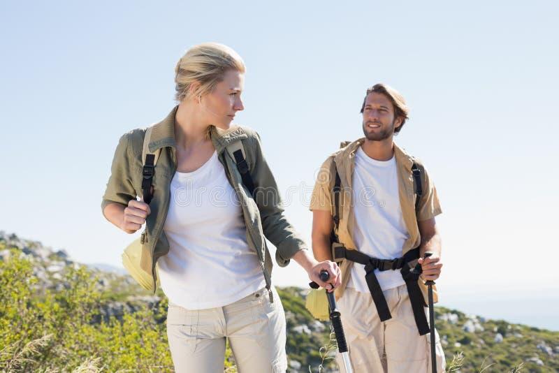 Привлекательные пешие пары идя на горную тропу стоковая фотография rf