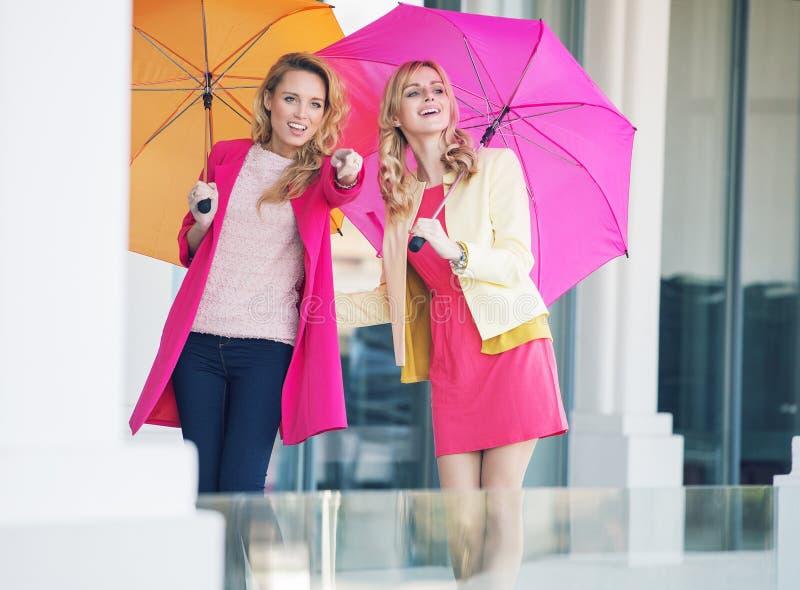 Привлекательные подруги с красочными зонтиками стоковое фото