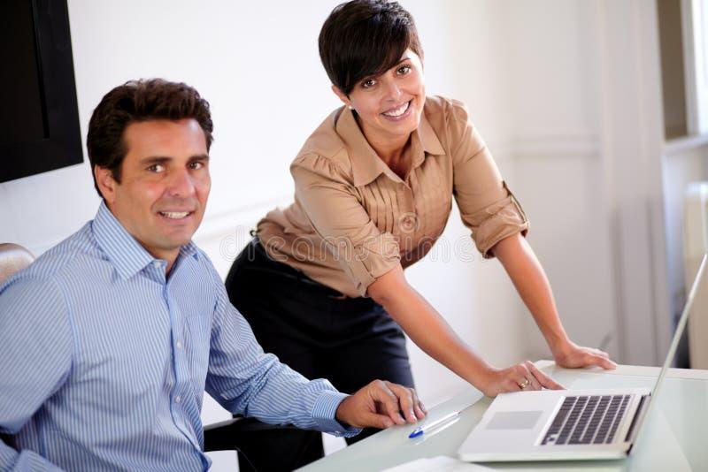 Привлекательные профессиональные пары усмехаясь на вас стоковая фотография rf
