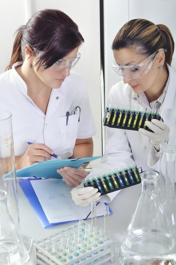 Привлекательные ученые студентов PhD детенышей наблюдая цветом переносят после destillation решения в химической лаборатории стоковое фото rf