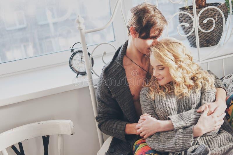 Привлекательные человек и женщина в прижиматься спальни совместно милый стоковые изображения rf