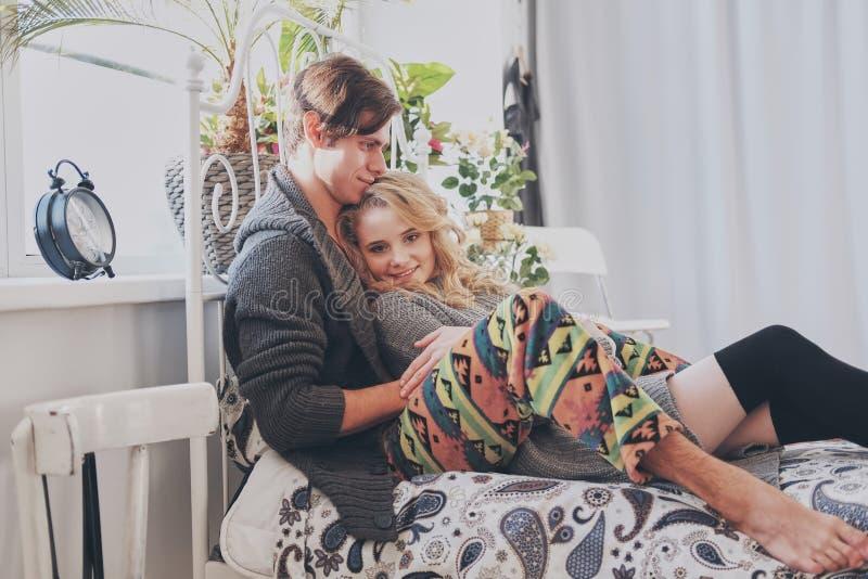 Привлекательные человек и женщина в прижиматься спальни совместно милый стоковая фотография rf