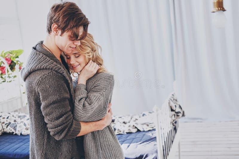 Привлекательные человек и женщина в прижиматься спальни совместно милый стоковое фото