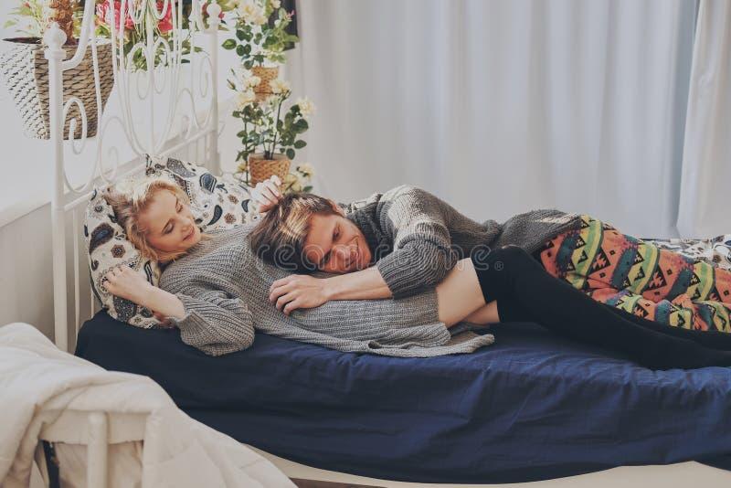 Привлекательные человек и женщина в прижиматься спальни совместно милый стоковое изображение rf