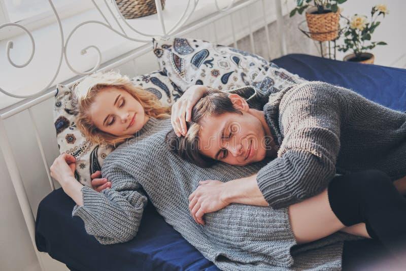 Привлекательные человек и женщина в прижиматься спальни совместно милый стоковое изображение