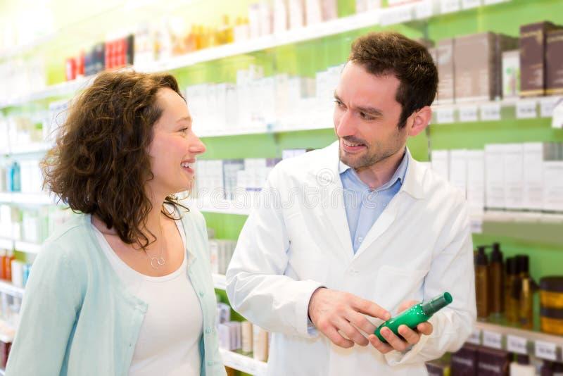 Привлекательный аптекарь советуя пациенту стоковое изображение rf