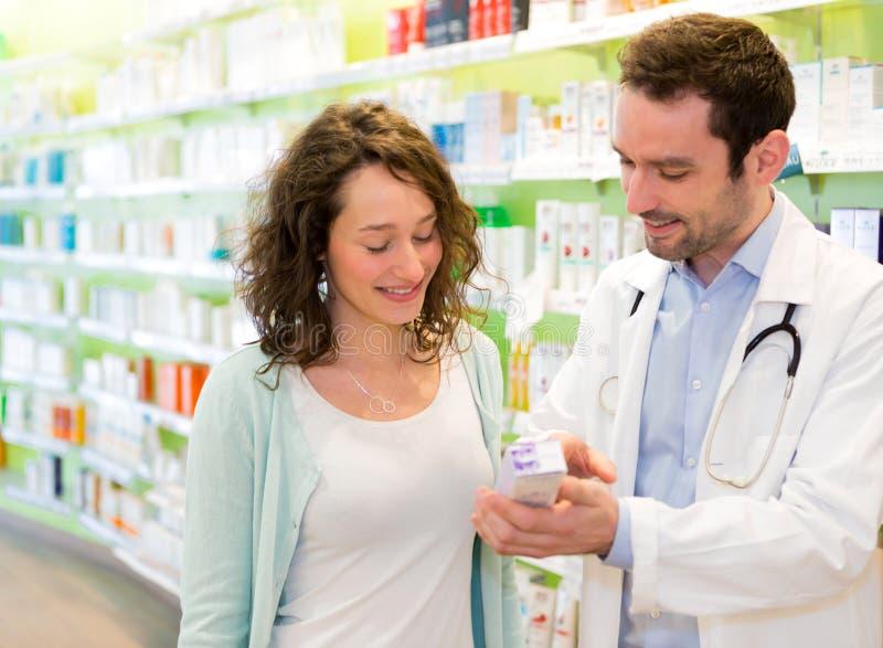 Привлекательный аптекарь советуя пациенту стоковое фото
