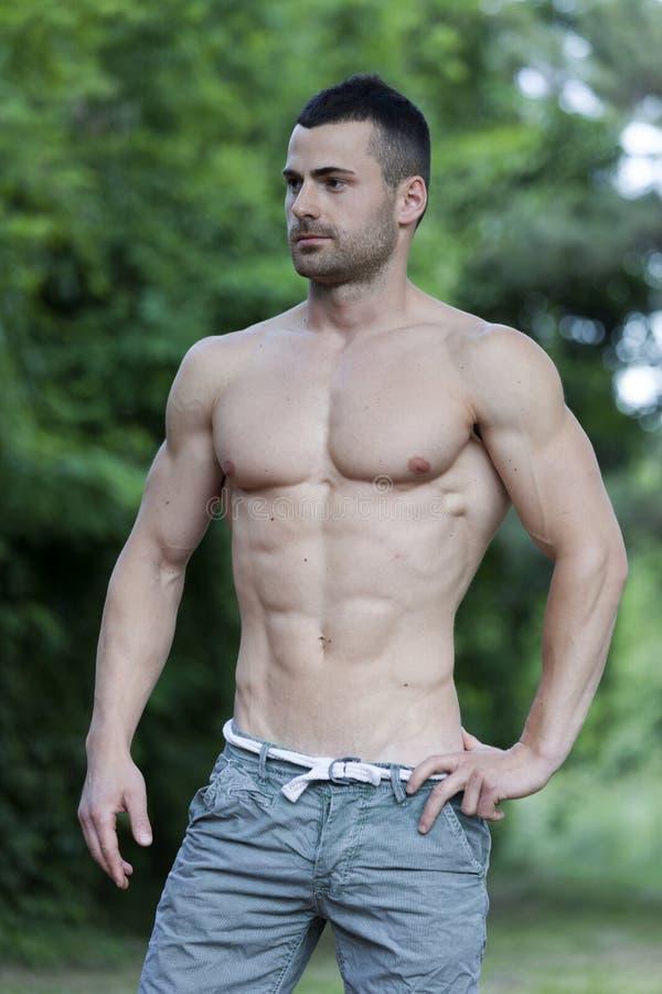 Привлекательный без рубашки молодой человек отдыхая после разминки в PA города стоковое изображение