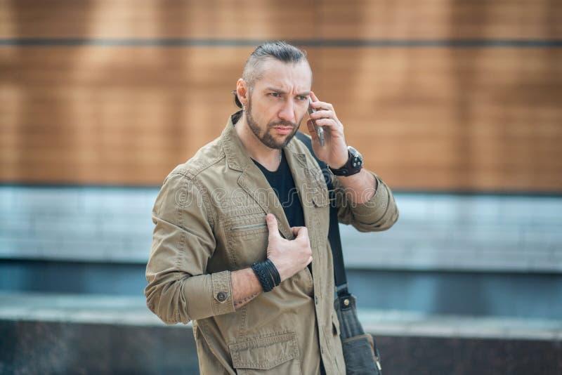 Привлекательный бизнесмен говоря на smartphone стоковые изображения rf
