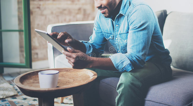 Привлекательный бородатый африканский бизнесмен используя таблетку пока сидящ на софе на его современном доме Концепция молодые л стоковое изображение rf