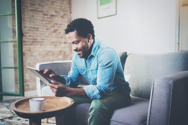Привлекательный бородатый африканский бизнесмен используя таблетку пока сидящ на софе на его современном доме Концепция молодые л стоковое фото
