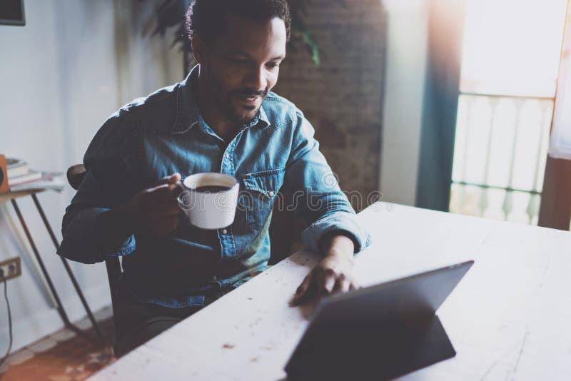 Привлекательный бородатый африканский человек делая видео- переговор через интернет с партнерами пока держащ кофе белой чашки чер стоковое изображение rf