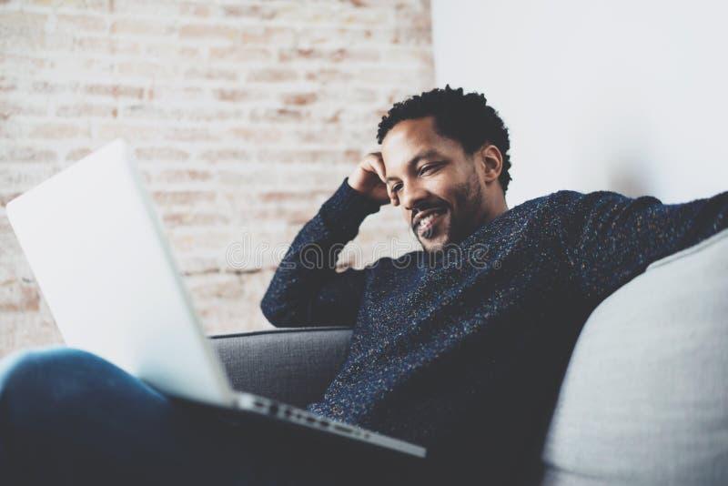 Привлекательный бородатый африканский человек используя компьтер-книжку пока ослабляющ софу на его современной домашней студии Ко стоковое изображение rf