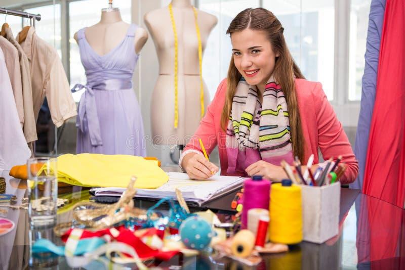 Привлекательный женский делать эскиз к модельера стоковые изображения