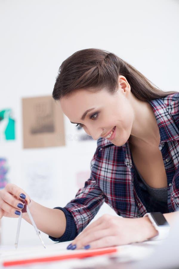 Привлекательный женский дизайнер работает на светокопии стоковые изображения