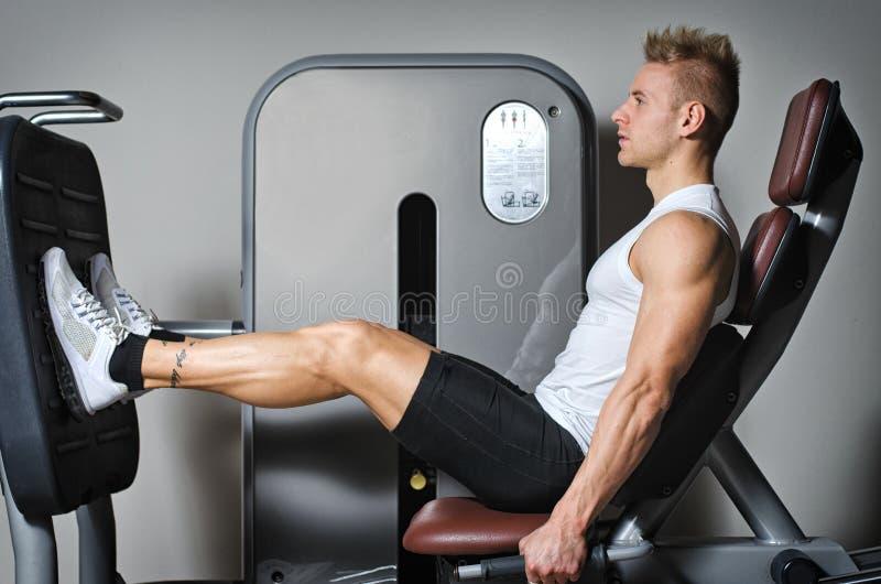 Привлекательный и подходящий молодой человек в спортзале разрабатывая ноги стоковая фотография rf