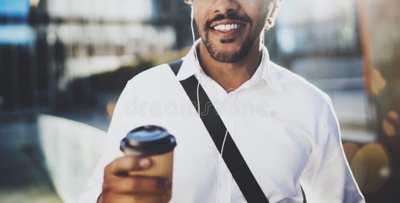 Привлекательный молодой американский африканский человек в наушниках идя на солнечный город с кофе взятия прочь и наслаждаясь для стоковые фотографии rf