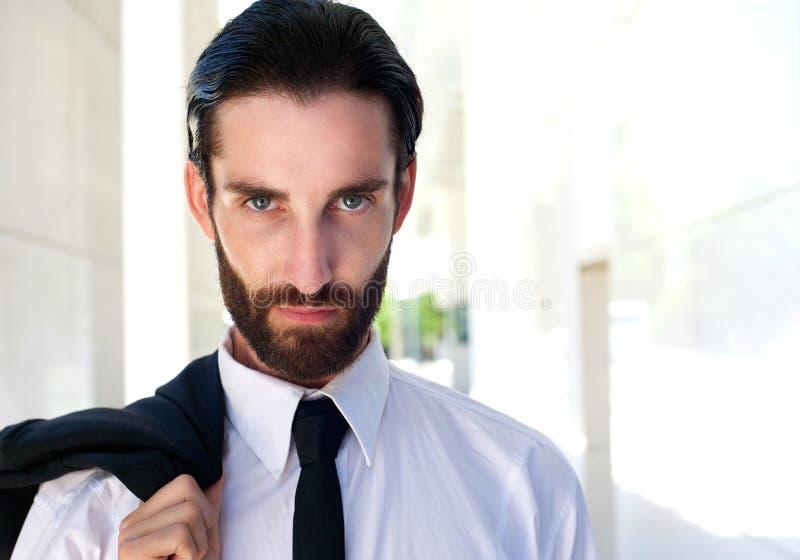 Привлекательный молодой бизнесмен с снаружи бороды стоящим стоковое фото rf