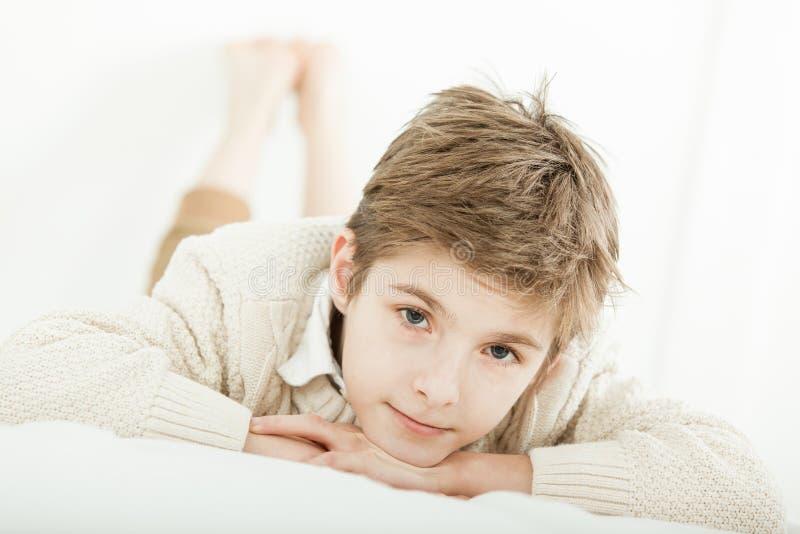 Привлекательный молодой мальчик ослабляя на его кровати стоковые изображения