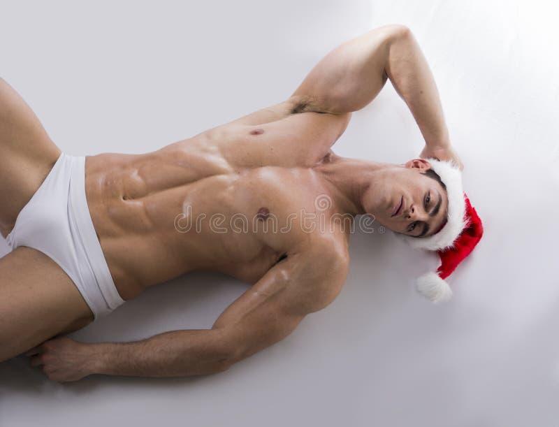Привлекательный молодой человек мышцы на поле в шляпе Санта Клауса красной стоковое изображение