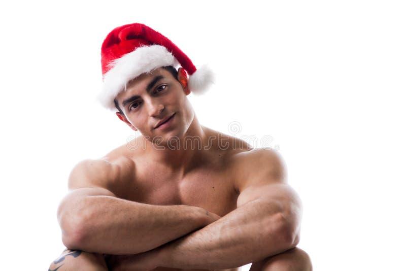 Привлекательный молодой человек мышцы сидя в шляпе Санта Клауса красной стоковая фотография rf