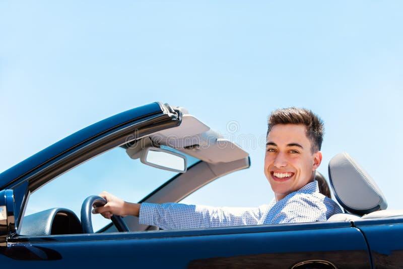Привлекательный молодой человек управляя автомобилем с откидным верхом стоковая фотография