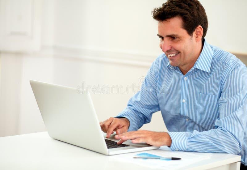 Привлекательный мужской предприниматель работая на его компьтер-книжке стоковые изображения rf