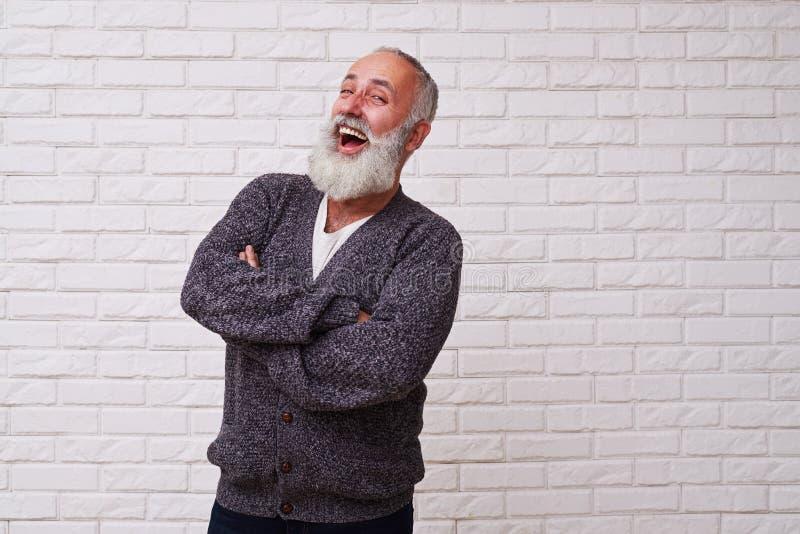 Привлекательный мужчина бороды смеясь над и стоя уверенно против стоковое изображение rf