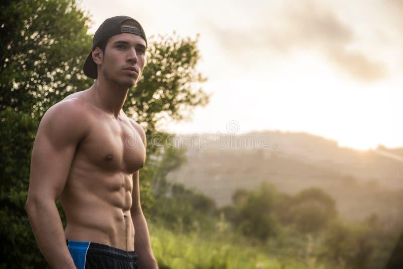 Привлекательный мышечный без рубашки молодой человек в природе стоковая фотография rf