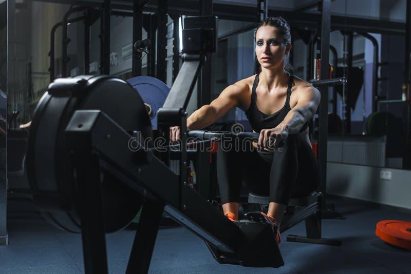 Привлекательный мышечный тренер CrossFit женщины делает разминку на крытом rower стоковые фото