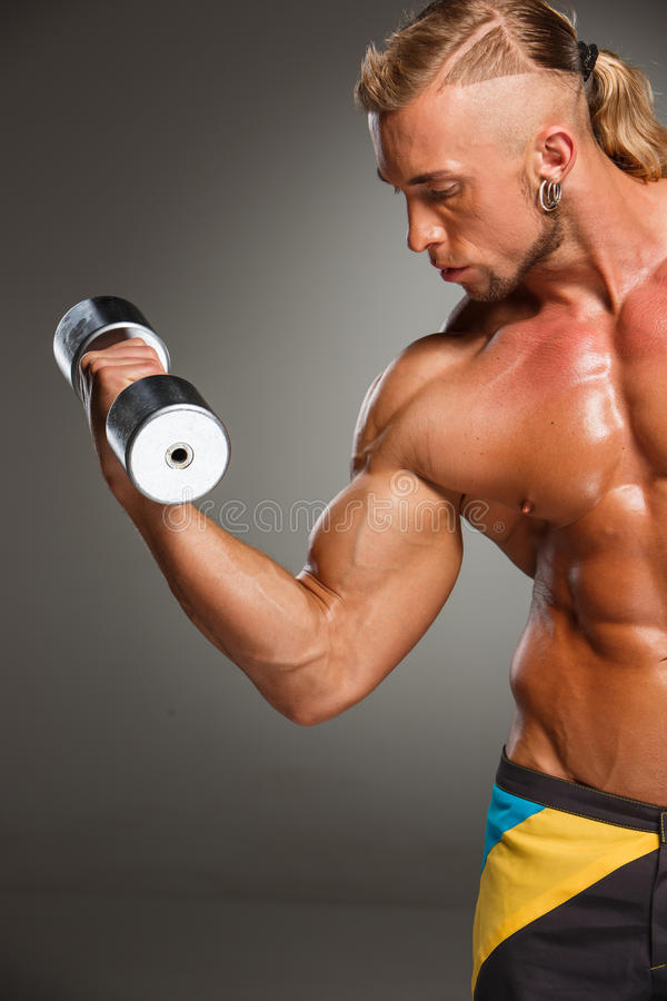 Привлекательный построитель мужского тела на серой предпосылке стоковые фото
