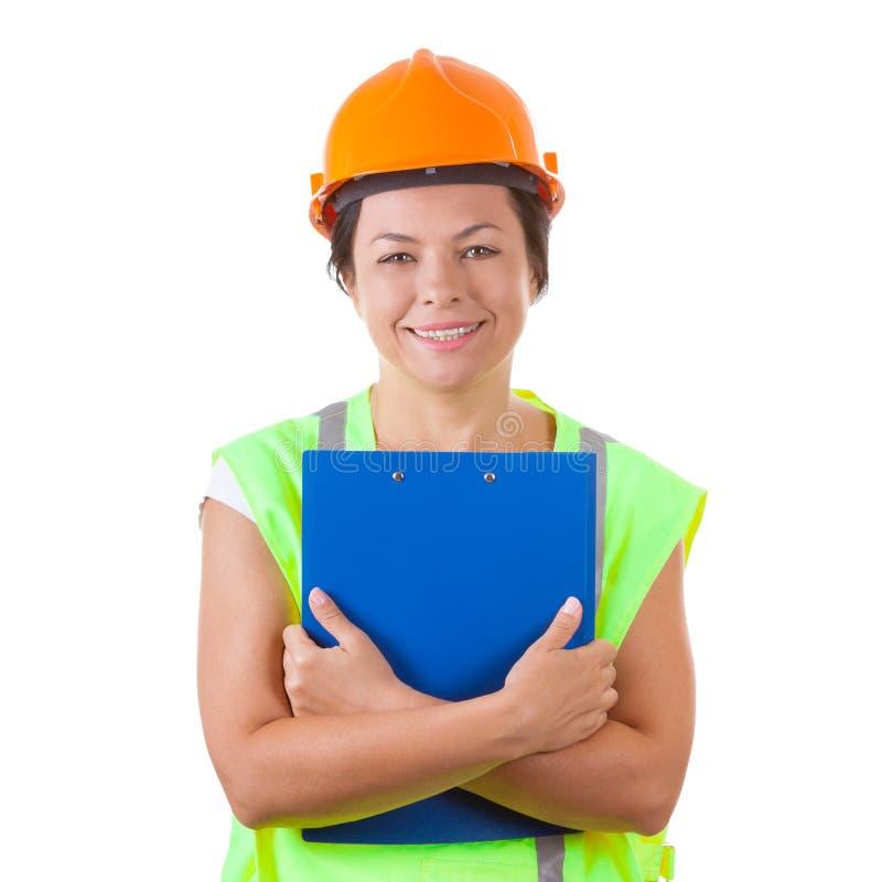 Привлекательный работник женщины в куртке безопасности и желтом шлеме Holdi стоковое изображение