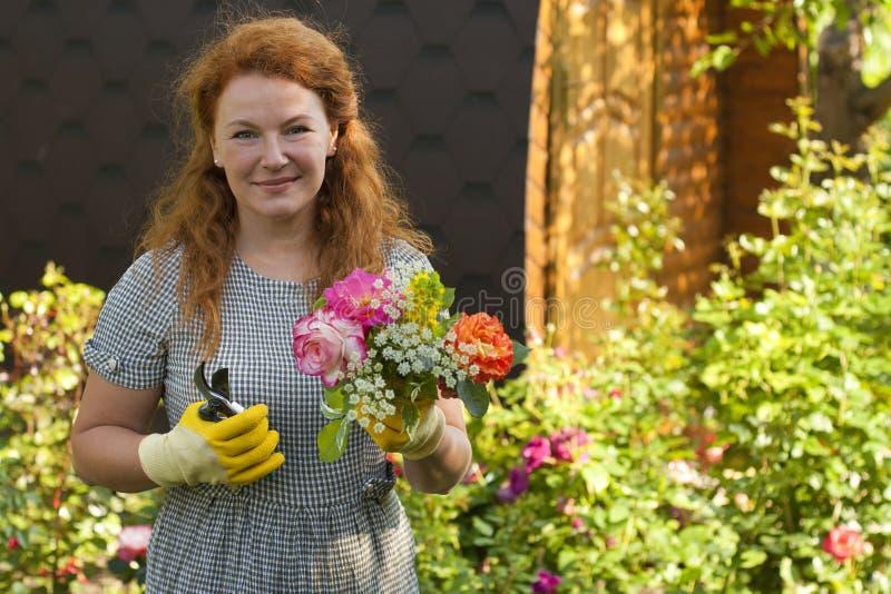 Привлекательный садовник взрослой женщины растет розы цветков стоковое изображение rf