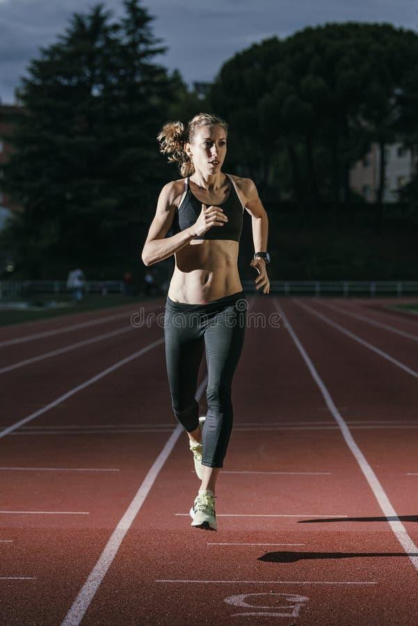 Привлекательный спортсмен следа женщины бежать на следе стоковая фотография rf