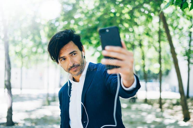 Привлекательный усмехаясь бизнесмен используя smartphone для listining музыки пока идущ в парк города Молодой человек делая selfi стоковое изображение