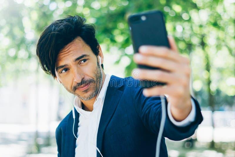 Привлекательный усмехаясь бизнесмен используя smartphone для listining музыки пока идущ в парк города Молодой человек делая selfi стоковое изображение rf