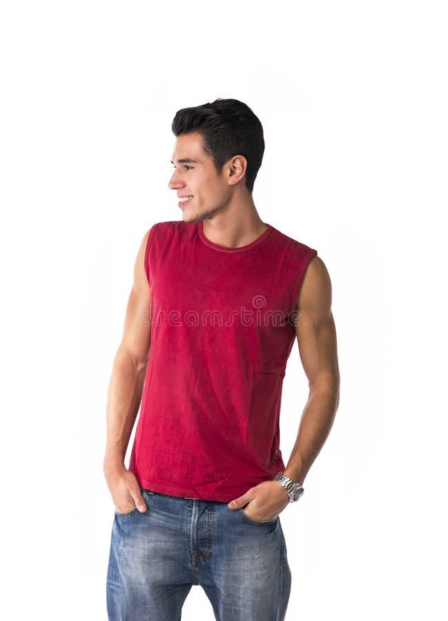 Привлекательный усмехаясь молодой человек смотря к стороне на пустом пространстве рядом с ним стоковые изображения