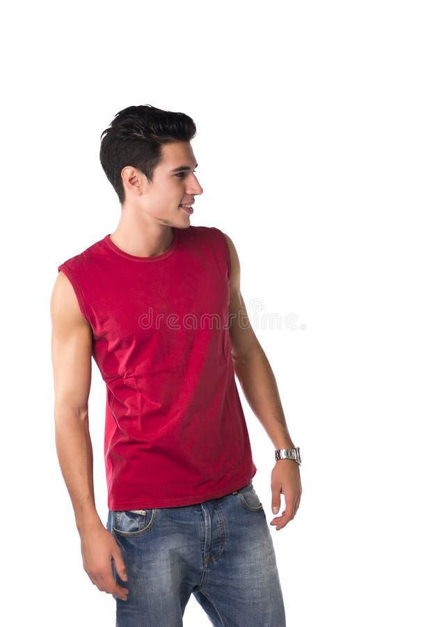 Привлекательный усмехаясь молодой человек смотря к стороне на пустом пространстве рядом с ним стоковое фото