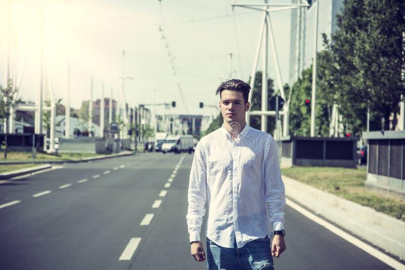 Привлекательный усмехаясь человек стоя в середине улицы города стоковое фото rf