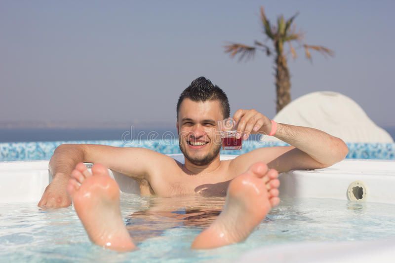 Привлекательный человек в бассейне с коктеилем стоковое фото rf