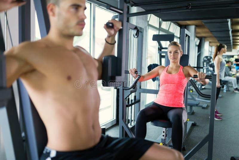 Привлекательный человек и красивая разминка женщины в спортзале стоковая фотография rf