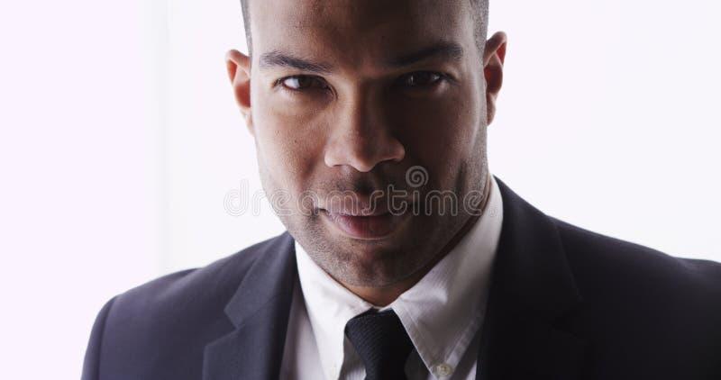 Привлекательный человек смотря костюм камеры нося стоковые изображения