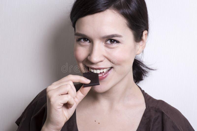 привлекательный шоколад есть детенышей женщины студии съемки стоковая фотография
